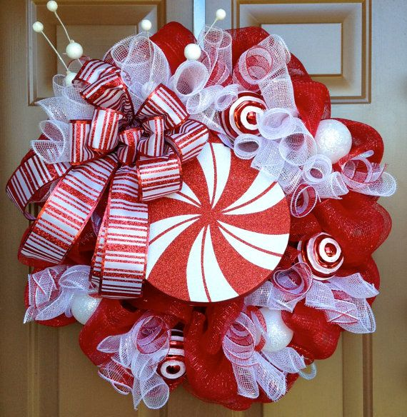 This wreath is decorated with a large peppermint, red and white ornaments, red mesh, white mesh, and christmas ribbon. The width is ~ 25.