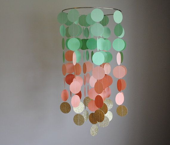 This mobile is made of 2 circles cut from a lightweight card stock in mint green, peach, and glittery gold. It is designed to hang from a