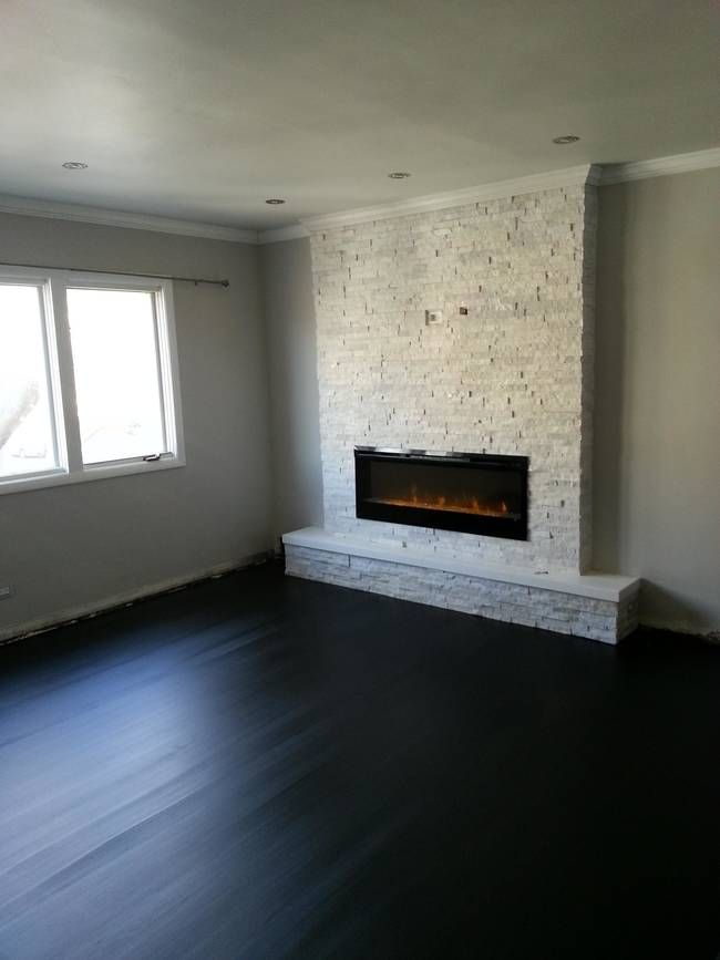The dark hardwood flooring! It provides the perfect contrast to the light stone on the hearth.