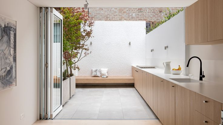 Benn + Penna has renovated and extended a dilapidated terraced in Sydney, creating a new kitchen with a long counter that continues into a courtyard
