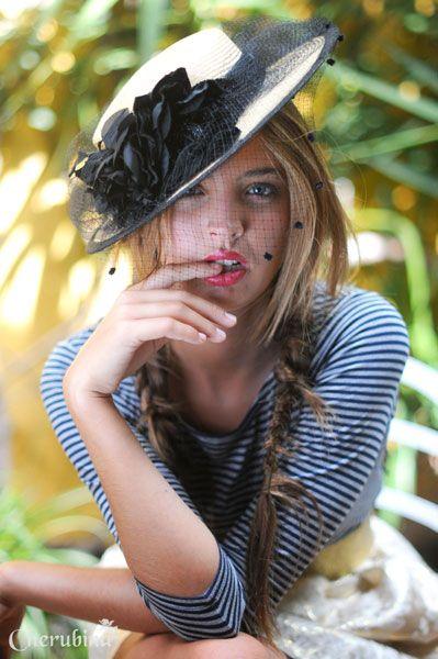 Sombrero de paja, de alas rectas y copa baja y plana rodeada por una cinta negra con flores . Ideal para invitadas a bodas