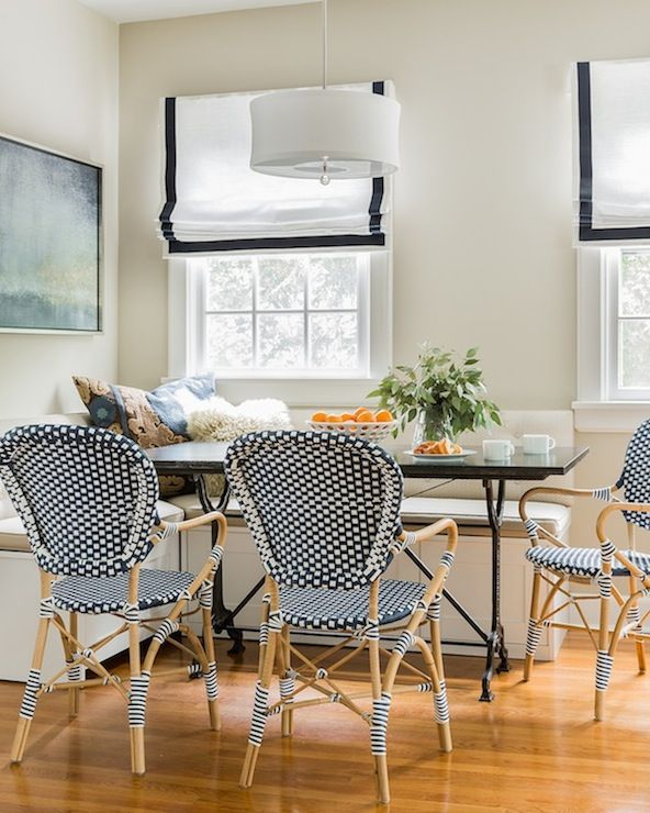 Elegant breakfast nook boasts L shaped built-in banquette placed under windows dressed in white and navy grosgrain roman shades paired with French iron dining table surrounded by Serena & Lily Riviera Armchairs in Navy illuminated by white drum pendant.