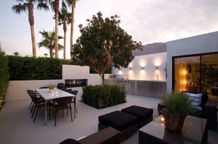 Contemporary Patio with exterior tile floors, Outdoor kitchen, Fence, Outdoor dining area, Outdoor fireplace
