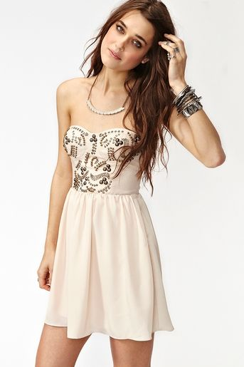 Super cute nude dress featuring a sweetheart neckline and mixed metal studs. Detachable/adjustable straps, lightly padded cups. Hook/eye and zip closures at side, fully lined. Looks perfect paired with a chunky cocktail ring and platforms! By Ladakh.