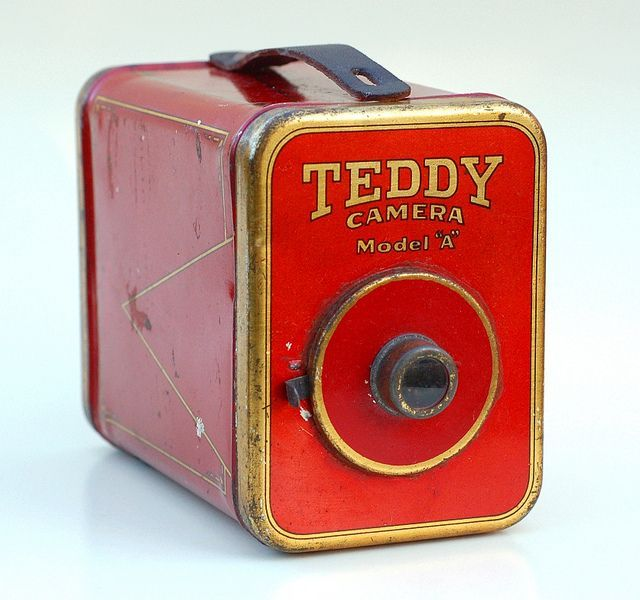 """The Teddy Camera is a stamped-metal box camera, made c.1924 by the Teddy Camera Company of Newark, NJ. The camera came with a set of sensitized cards, and made 2"""" x 3½"""" prints, developed on-the-spot within a tubular developing tank which attached to the bottom. From John Kratz."""