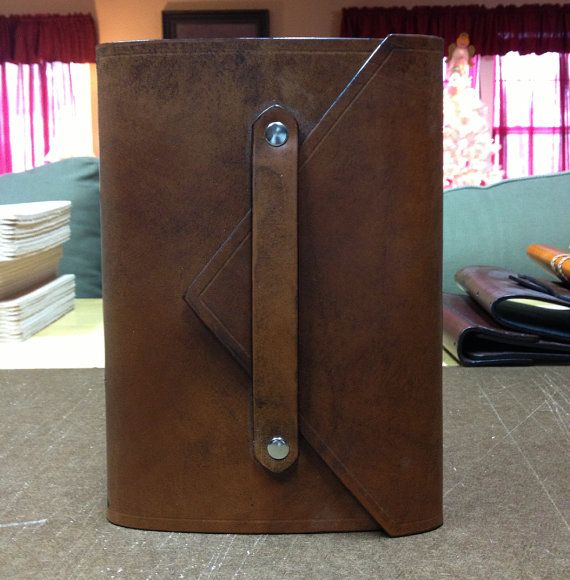 A refillable book binding for travel!  Leather strap attached to cover using metal snaps. Cover flap slides under strap.