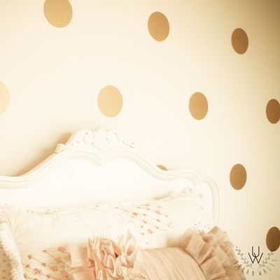 Metallic gold polka dot wall decals placed on a beige wall behind a victorian style bed headboard. The polka dots are equally spaced over the wall.