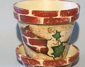 This 4 inch clay pot and saucer has been sponge painted cream, light rust and beige, then shaded and stamped with rectangle shaped bricks to resemble a broken brick wall. Then ivy was painted on for a garden look. I would recommend slipping your potted plant into the clay pot to keep the pot clean. The pot measures 4 across and 3.75 tall. The candle is NOT included.