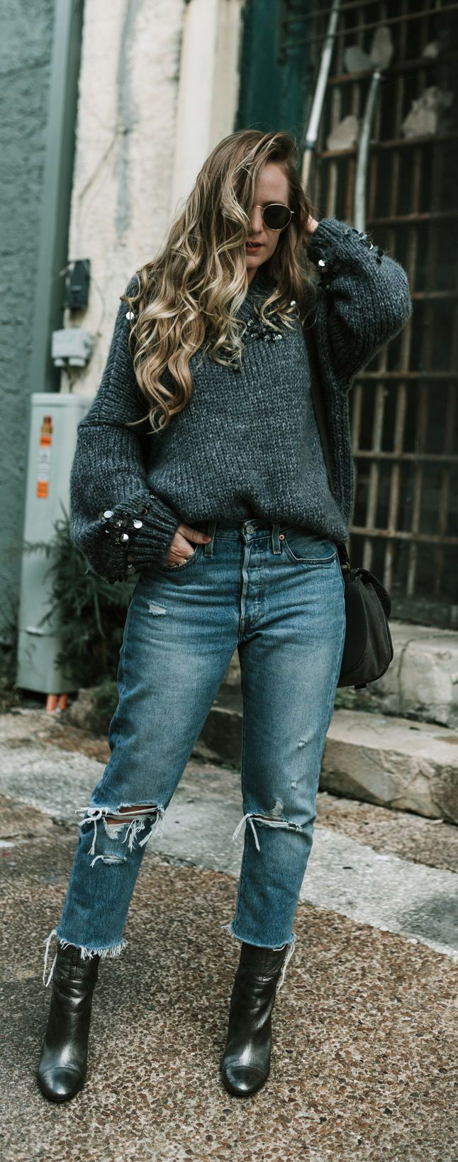 Edgy winter look styled with sequin embellished oversized sweater, distressed Levi jeans and metallic booties #edgywinteroutfit #sequinsweater #winteroutfit