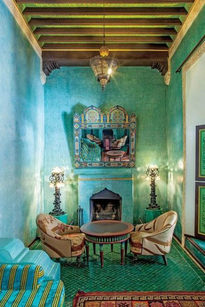 Blue and green take this Moroccan-inspired room to a whole new level. We love the shape of the fireplace and light fixture hung from the tall ceiling!