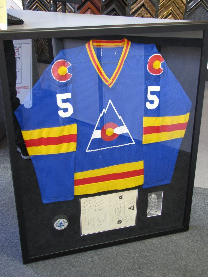 Original game worn Colorado Rockies NHL jersey, puck, autographed program, and photograph. The Colorado Rockies were the first NHL team to play in Denver from 1976 to 1982. They later became the New Jersey Devils.