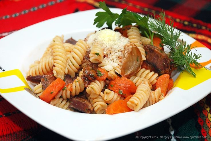 Вкусная паста сговядиной, приготовленная в бульоне и смешанная с обжаренными овощами и томатным соусом, с зеленью и пармезаном