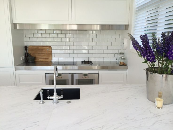 A classic style to this kitchen, with 100x200 subway tiles. A black sink, Framed door style, Stainless steel work bench and pelmet add interest, as does the Tom Dixon chopping board. designed by Hayley Dryland of Bespoke on Khyber