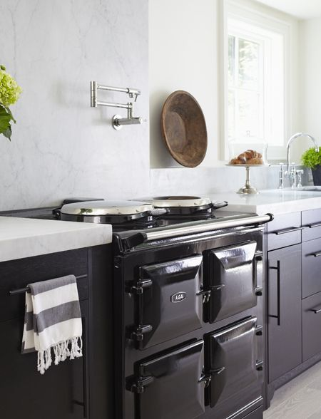 The ultimate kitchen would have an AGA range! I also love the marble countertop, continued up the wall in this kitchen. It is a simple and clean look, which adds to the elegance of this modern style farmhouse. Princess Margaret Showhome 2012 | House & Home