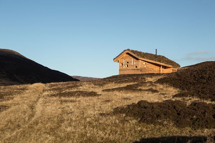 the scheme draws from modernist architecture and features roof covered in heather, moss and stone, allowing the hut to camouflage in the highland landscape when viewed from above.