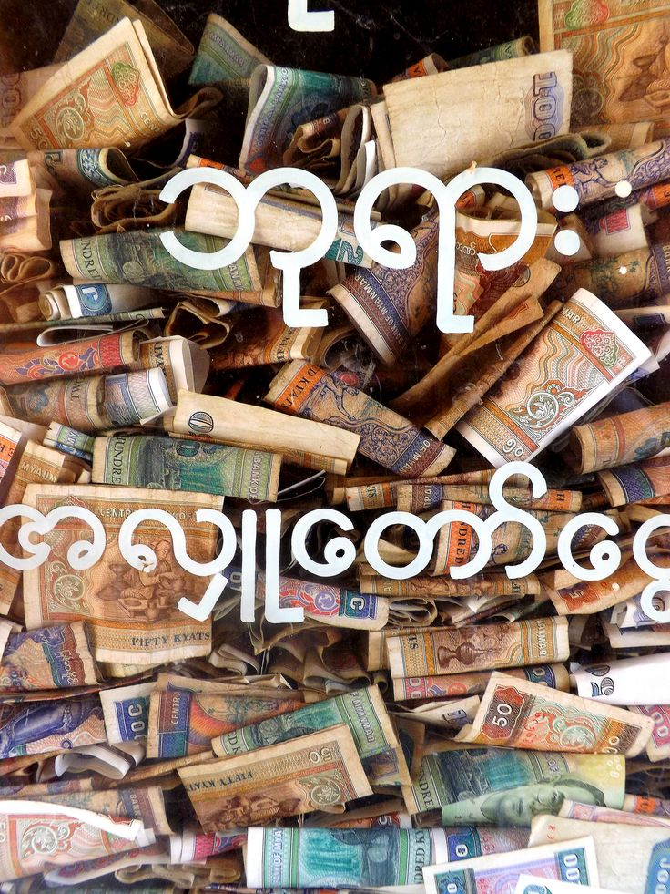 Colourful patterns and intricate details of Burmese money taken while travelling around Burma. A close-up photograph of donations behind glass in the entrance of a temple in Bagan, Myanmar. (2014)