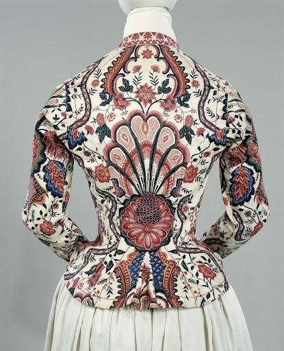 """""""Jak van sits, dat op een crèmekleurig fond grote bloemen en ruitpatronen toont, met als hoofdkleuren paars, roze, blauw en blauwgroen. Afwerking met roze-wit langettenband., anoniem, 1810 - 1820."""" The word 'sits' means chintz: """"sits (katoen bedrukt met bloem- of bladmotief)"""""""