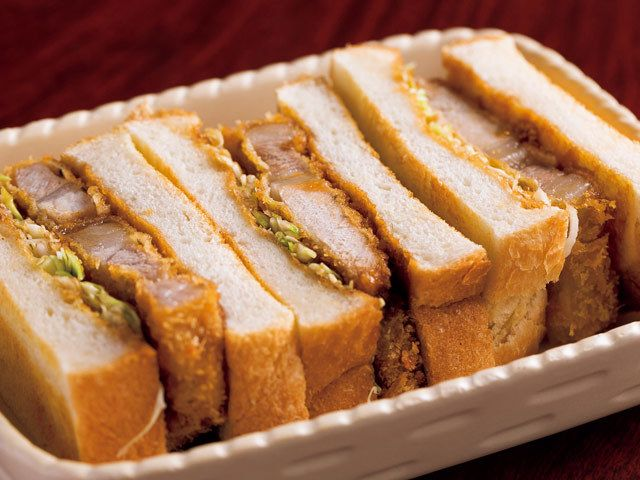 《 銀座 》「カツサンド」。白金豚の厚さは1cm 近く、ボリューム満点で脂が軽い  深夜でも絶品カツサンドが味わえる  『厨房酒場 カモメセラー』  銀座  カツサンドに使われる白金豚の厚さは1cm 近く!ボリューム満点で、脂が軽くて実に旨い。サンドにはほかに、メンチカツやビーフカリーなども用意。白金豚のカツは単品でもオーダーすることができ、さらにポークソテーにしてもらうことも可能なのだ。   店名のカモメとは出身地である岩手・大船渡の市の鳥。だから、三陸産の食材を一番に考え、名物のカツサンドなら白金豚、そのほか、海草やキノコなどは岩手産を選んでいる。   店の佇まい、主人・佐々木徹勝氏の立ち居振る舞いは、完全にオーセンティックバー。しかし60品はあるという、フードの充実に目を見張る銀座の一軒である。ラストオーダーは26時。深夜に食べるカツサンド……背徳を感じるが、美味しさは保証できる。