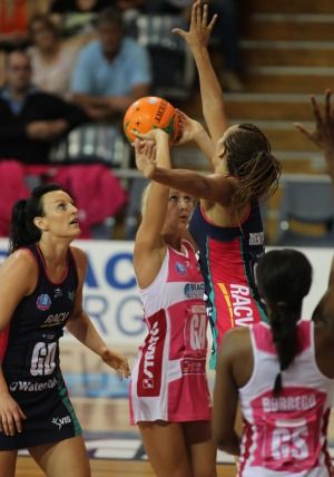 Bianca Chatfield looks on as teammate Geva Mentor goes up to try and block s hot by Erin Bell of the Queensland Firebirds,