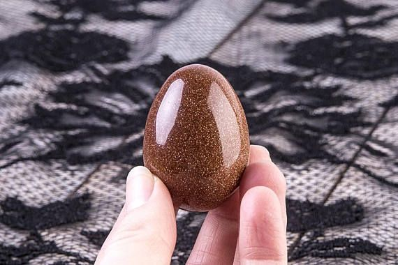 This Goldstone egg is such a beautiful, glittery stone. It is a brownish orange color with tiny specks of copper throughout, making for a truly magical appearance.  Goldstone is known as the stone of ambition, known to aid in the achievement of ones goals. It can also revitalize your personal energy field and stabilize the emotions.  A man-made stone, crafted with tiny copper specs, Goldstone has many of the metaphysical properties of copper (abundance, good luck, and confidence).  This…