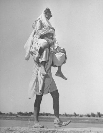 A Sikh man carrying his wife on his shoulders, migrating to Punjab after the partition of India, 1947.  Photograph by Margaret Bourke-White