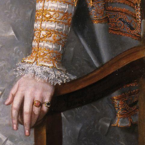 Dettagli 3. Alonso Sanchez Coello: Anna d'Austria, regina di Spagna. Olio su tela del 1571. Museum Lazaro Galdiano, Madrid. La regina si appoggia al sediolone: la sua manica rigidamente pieghettata e ricamata in oro, lascia uscire un bellissimo polsino al tombolo: dietro scende, grigia e ricamata in oro anche lei, la manica a prosciutto ( larga sopra e stretta sotto) del soprabito. Opulento, come tutti gli abiti dei nobili dell'epoca.
