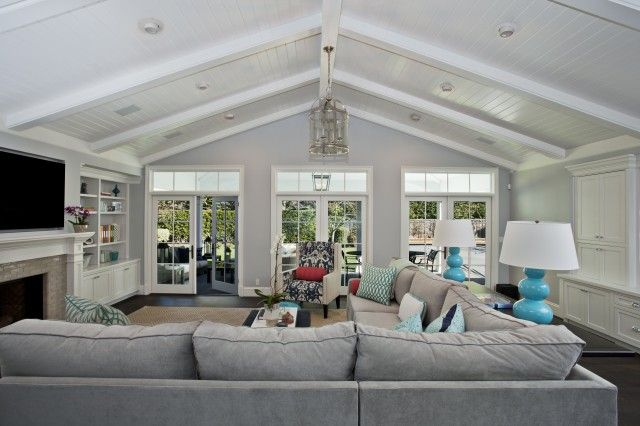 Gray sofa fabulous family room design with Robert Abbey Triple Gourd Table Lamps in Egg Blue, gray velvet sectional sofa with Z Gallerie Geo Pillows in Aquamarine, TV, built-ins, gray glass tiles fireplace surround, gray walls paint color, beadboard sloped ceiling and French doors.
