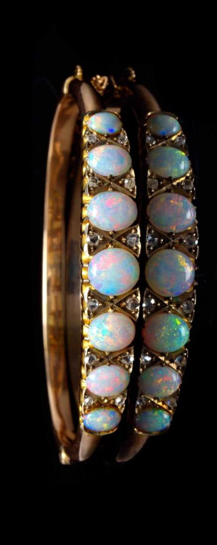 A Yellow Gold, Opal and Diamond Bangle Bracelet, containing seven oval cabochon cut opals weighing approximately 6.00 carats total and 12 rose cut diamonds accents, hinged base. 9.10 dwts.