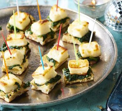 Naan, Spinach and halloumi bites: Wilt spinach with garlic and spices, then pile onto small, warm pieces of naan bread and top with halloumi for an attractive vegetarian canapé