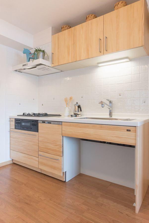 木目が美しい無垢材を使用したシステムキッチン 真っ白なレンジフード