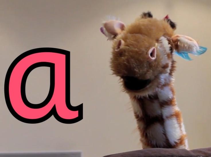 Geraldine Giraffe searches for items to represent the letter a