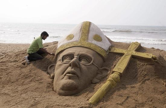 El artista indio Sudarshan Pattnaik hace una escultura de arena del nuevo papa Francisco en una playa cercana a Bhubaneswar, en la India.      Foto de Agencia EFE.