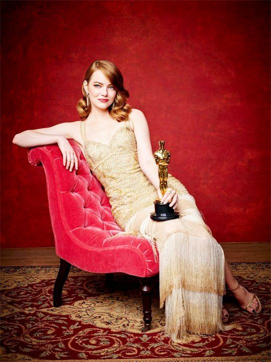 "Emily Jean ""Emma"" Stone with her Oscar trophy as Best Actress in La La Land as she sat in a red lounge chair."