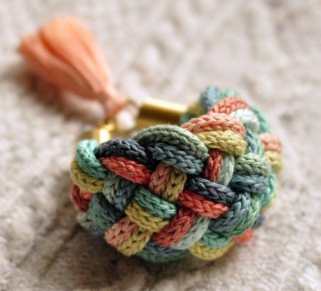 Un bracelet manchette réalisé en tressant plusieurs brins de tricotin entre eux.
