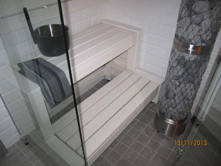 Valkoiset puupinnat, laattaseinät yhdistettynä lasiseiniin, lauteet AL runkoiset kippilauteet.Sauna 1,6m2, rakennettu kylpyhuoneen perälle