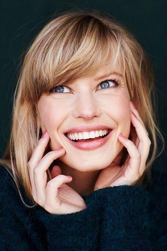 Улыбающаяся голубые глаза белокурая женщина в студии, Глядя вверх стоковое фото