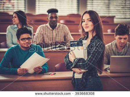 Multinational group of cheerful students taking an active part in a lesson while sitting in a lecture hall.
