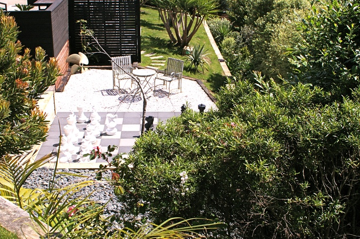 A view from top lawn of giant chest board & seating area by Fusion Landscape Design. www.fusionlandscapedesign.co.nz