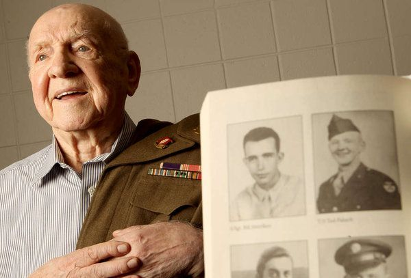 Ted Paluch holds his old uniform next to a book about the Malmedy massacre of December 1944.