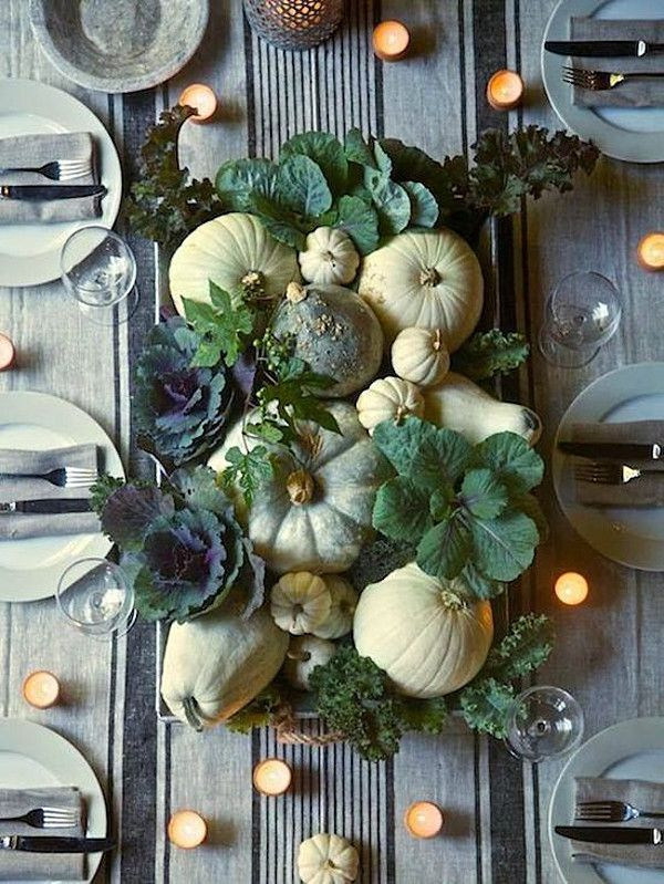 Thanksgiving centerpiece made with pumpkins, gourds, and leafy greens!