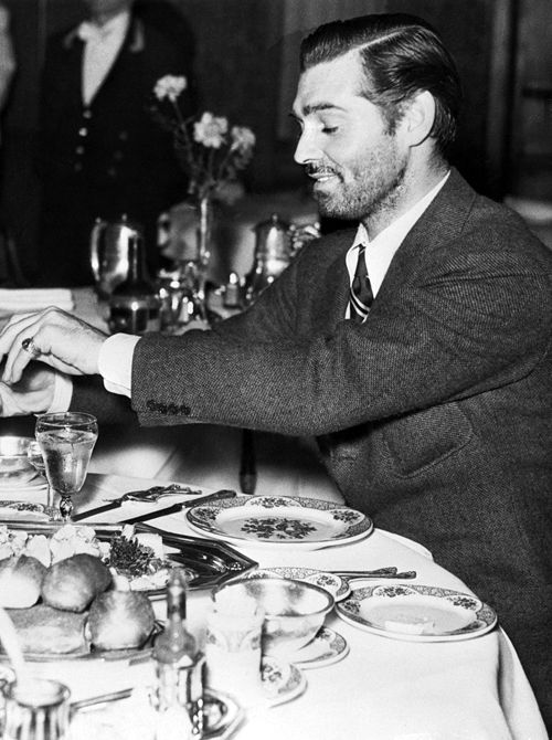 A bewhiskered Clark Gable dines on the set of The Call of the Wild, 1935