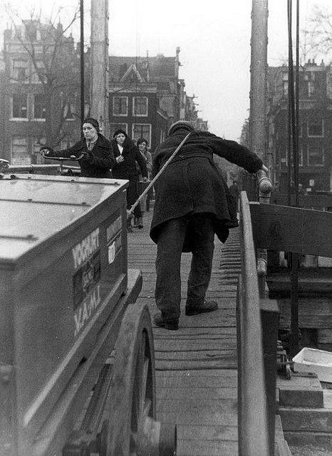 """Een bruggentrekker, """"kar-ga-door"""" in de volksmond, aan het werk [op de Magere Brug] in Amsterdam. Bruggentrekkers trokken voor een vergoeding zware karren over de steile bruggen over de grachten in de stad. Februari 1934. [Later is men de term """"cargadoor"""" gaan gebruiken voor de scheepsmakelaar, als tussenpersoon betrokken bij het beladen en lossen van schepen]."""