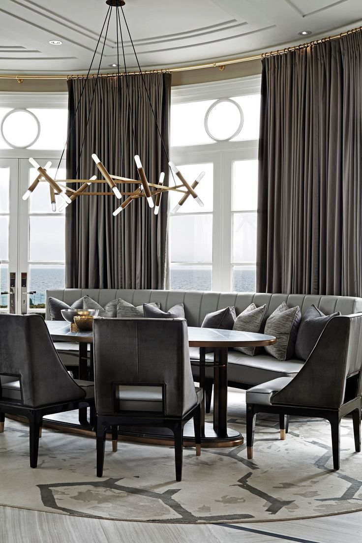 A casual breakfast nook is dominated by a curvaceous banquette and lighting designed by Rafauli.