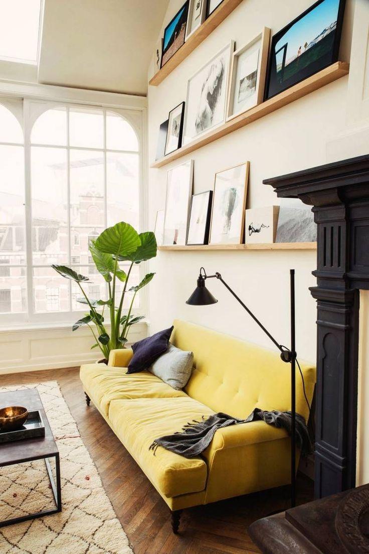 gelbes Sofa und Holz Wandregale an der Wand dahinter