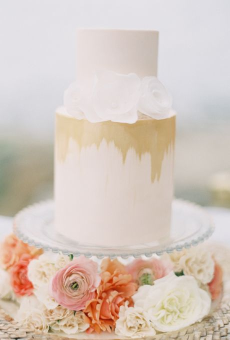 Brides.com: 29 Glam Metallic Wedding Cakes. A two-tiered white wedding cake with gold details and flower accents, from Hey There, Cupcake.