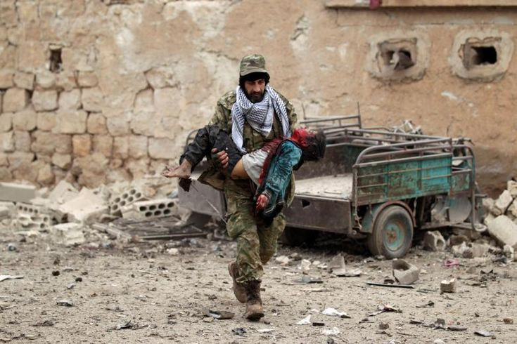 A rebel fighter carries an injured boy after a car bomb explosion in Jub al Barazi east of the northern Syrian town of al-Bab, Syria, January 15.     REUTERS/Khalil Ashawi