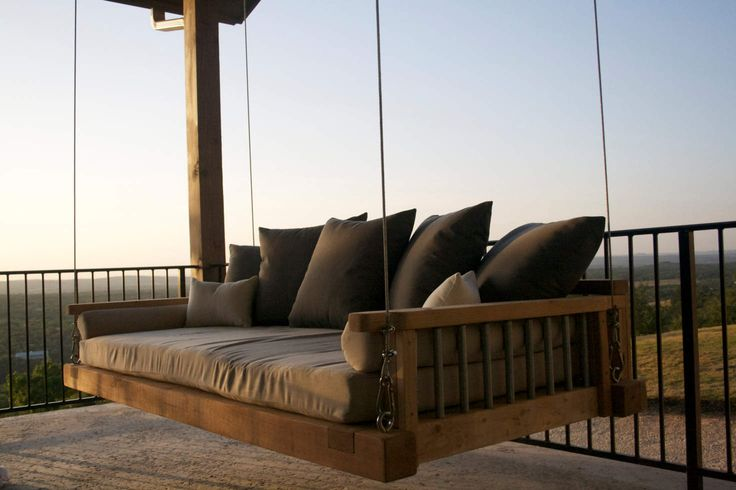 Cedar swing bed suspended by galvanized cable with outdoor mattress and pillows