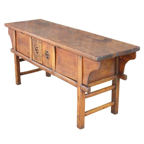 This antique farmhouse console features traditional Chinese design, holding a double door compartment on its front for storage, elm molding details, and a clean natural finish.  Details:  Era: Vintage Dimensions: L= 62, D= 18, H= 27 Material: elm Color: natural Condition: good  White Glove Shipping quote is $ 299 to most US Cities ( Excludes Hawaii & Alaska ). Price might suffer minor changes once we receive Final shipping destination. Approximate White Glove delivery times 7-14 business…