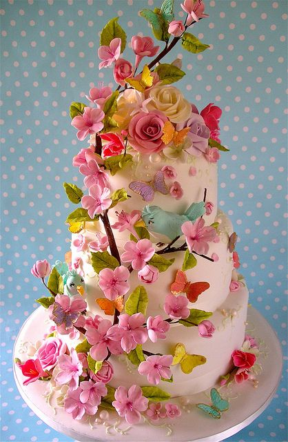 OMG I adore this cake.  The colorful flowers, the pearl accents, and the birds peeking through the branches at each other.  It totally reminds me of Mary Poppins!