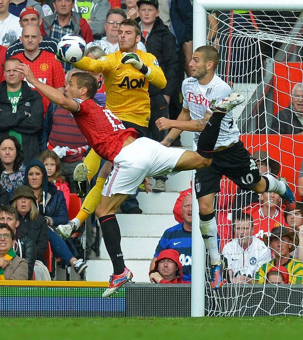 Manchester United's Spanish goalkeeper David de Gea punches the ball into Nemanja Vidic's heel whilst under pressure from Fulham's Croatian striker Mladen Petric, resulting in an own goal by Nemanja Vidic
